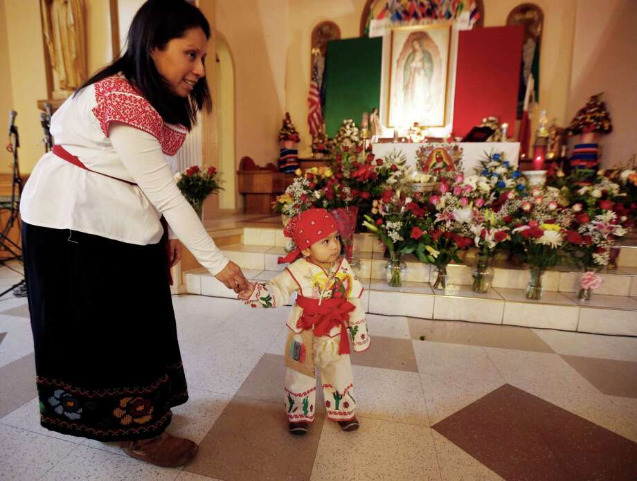Maricela Cruz, left, holds her 18-month-old son, Henry Cruz, while visiting a shrine to the Virgin of Guadalupe during the virgin's feast day celebration at Our Lady of Fatima Church, Wednesday, Dec. 12, 2012, in Passaic, N.J. Catholic Mexicans living in New Jersey pay homage to the Virgin on Dec. 12, to observe what they believe was an apparition of the Virgin seen by Juan Diego, an indigenous man, on the hill of Tepeyac in Mexico City on Dec. 12, 1531. (AP Photo/Julio Cortez) Photo: Julio Cortez, Associated Press / AP