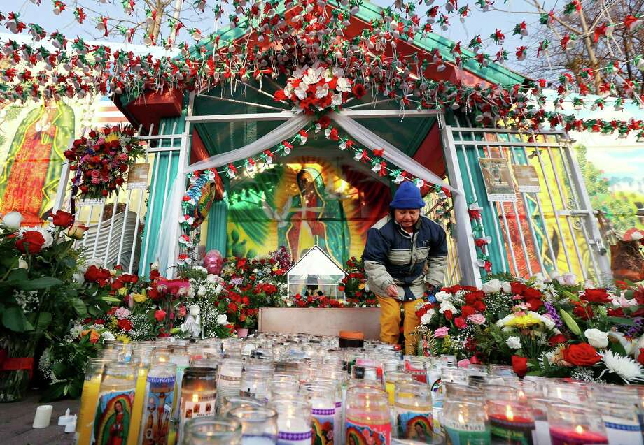 Teresa Martinez arranges flowers in front of a tree stump believed to have the image of Virgin of Guadalupe as the roadside shrine is decorated on the Virgin of Guadalupe feast day, Wednesday, Dec. 12, 2012, in Passaic, N.J. Catholic Mexicans living in New Jersey pay homage to the Virgin on Dec. 12, to observe what they believe was an apparition of the Virgin seen by Juan Diego, an indigenous man, on the hill of Tepeyac in Mexico City on Dec. 12, 1531. (AP Photo/Julio Cortez) Photo: Julio Cortez, Associated Press / AP
