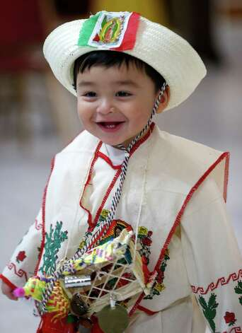 Joseph Villanueva, 18-months, is dressed in Mexican indigenous clothing during a celebration of  Virgin of Guadalupe's feast day at Our Lady of Fatima Church, Wednesday, Dec. 12, 2012, in Passaic, N.J. Catholic Mexicans living in New Jersey pay homage to the Virgin on Dec. 12, to observe what they believe was an apparition of the Virgin seen by Juan Diego, an indigenous man, on the hill of Tepeyac in Mexico City on Dec. 12, 1531. (AP Photo/Julio Cortez) Photo: Julio Cortez, Associated Press / AP