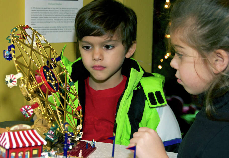 Jake and Sedona Taylor, 6-year-old twins from New Fairfield, are enchanted by a miniature Ferris wheel they discover at Merwinsville Hotel during Gaylordsville's Nov. 30 and Dec. 1, 2012 holiday festivities. Photo: Trish Haldin