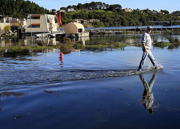 Jim Woessner walked home to Sausalito from the highway 1 at highway 101 near Mill Valley. King tides in the Bay Area caused some flooding in Marin County Wednesday December 12, 2012 and many beaches were partially covered. Photo: Brant Ward, The Chronicle