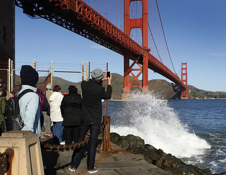 Tourists watch waves crash into the rocks at Fort Point during the king tide in San Francisco, Calif. on Tuesday, Dec. 11, 2012. Photo: Paul Chinn, The Chronicle