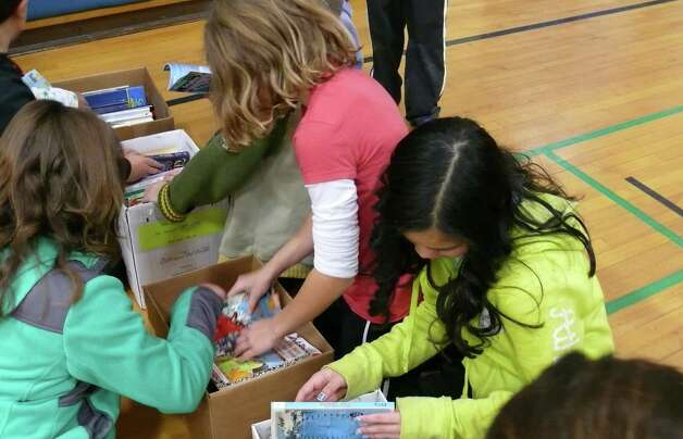 Fifth grade students at Holland Hill search through boxes of books donated by McDonald's. Photo: Genevieve Reilly / Fairfield Citizen