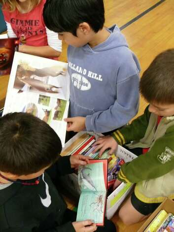 Fifth-grade students at Holland Hill search through boxes of books donated by McDonald's.Fairfield, CT 12/12/12 Photo: Genevieve Reilly / Fairfield Citizen