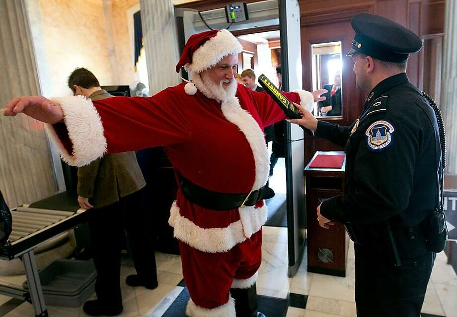 """You forgot to make him take off his belt:A Capitol Hill police officer checks Santa Claus with a metal-detecting wand at the Capitol in Washington. Santa was visiting Speaker of the House John Boehner to urge him to pass pending """"fiscal cliff"""" legislation before Christmas. Photo: Win McNamee, Getty Images"""