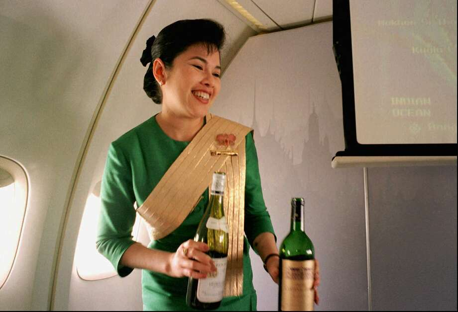 A Thai Airways International airline flight attendant offers a passenger a selection of wine during a flight from Singapore to Bangkok. Airlines have found a way to take the edge off the stress of flying. Photo: Richard Vogel, STF / AP