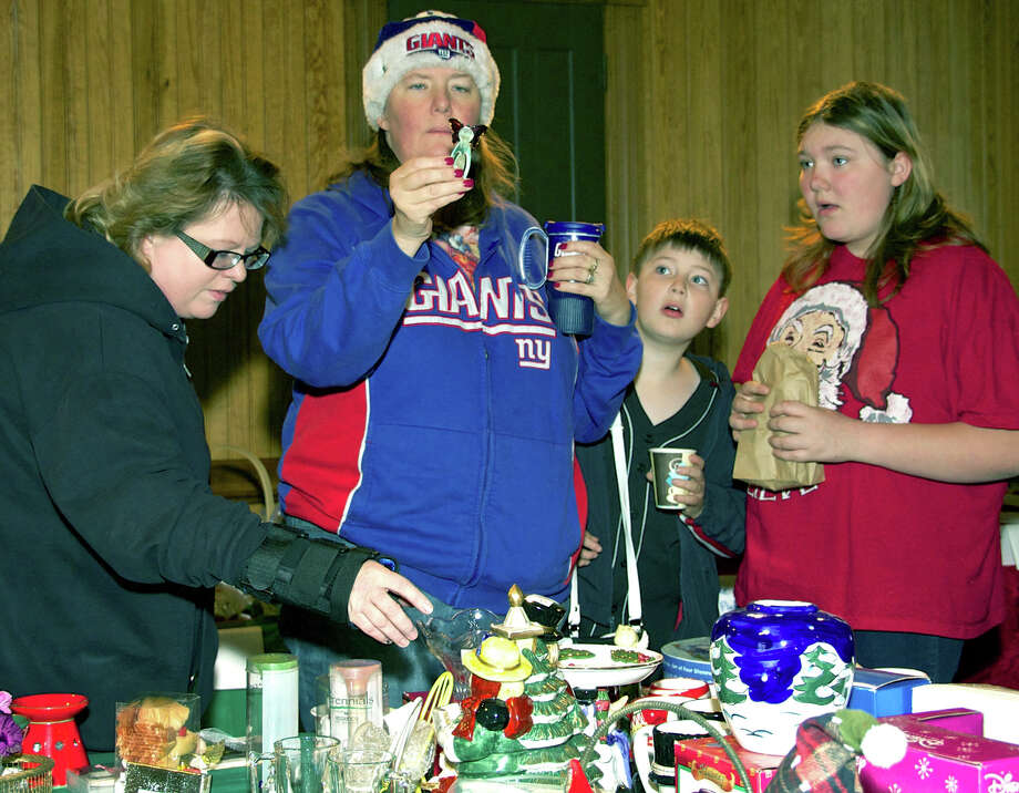 Captivated by the many items for sale are, from left to right, Lori Hoffman, Patty Shaw, John Shaw, 11, and Melanie Shaw, 13, who found time Dec. 1, 2012 to volunteer at the Animal Welfare Society's holiday bazaar at the railroad station in New Milford. Photo: Norm Cummings