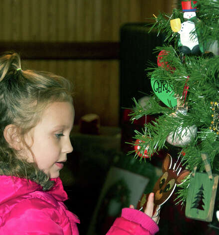 Checking out the lively ornaments adorning a small Christmas tree is Calley Thierfelder, 5, of New Milford during the Animal Welfare Society's holiday bazaar at the railroad station in New Milford. Dec. 1, 2012 Photo: Trish Haldin
