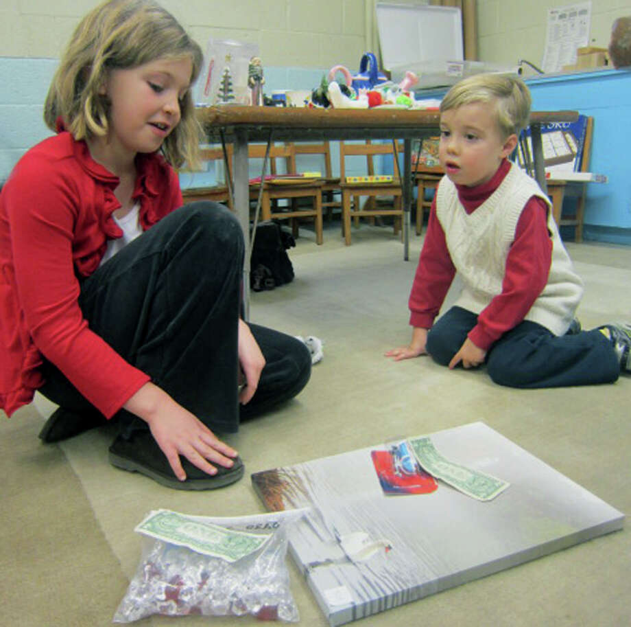Kyra Briggs, 8, of Sherman and her little brother, Nolan, 4, talk strategy about the Christmas gifts they've already purchased for their parents and what else they might want to buy at the Sherman Congregational Church's annual holiday fair. Dec. 1, 2012 Photo: Norm Cummings