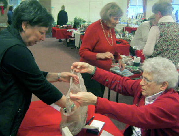 Church volunteer Julie Reppenhagen helps Brigitte Banach of Sherman organize her purchases at the Sherman Congregational Church's annual holiday fair. Dec. 1, 2012 Photo: Norm Cummings