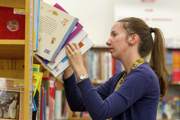 Employee Abby Weber shelves books at Half Price Books at Stone Ridge Market on Monday, Dec. 3, 2012. Photo: Michael Miller, San Antonio Express-News / © San Antonio Express-News