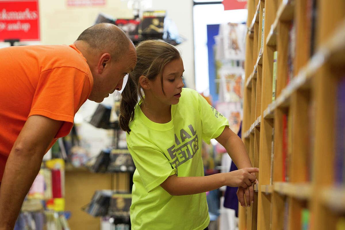Payton Saiz, 10, picks out books with her father, Lawrence, at Half Price Books at Stone Ridge Market on Monday, Dec. 3, 2012.
