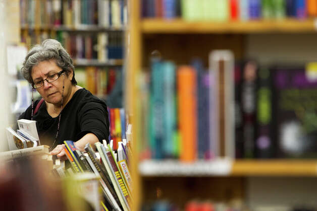 FOR BUSINESS - Lucille Barrios browses the selection at Half Price Books at Stone Ridge Market on Monday, Dec. 3, 2012. MICHAEL MILLER / FOR THE EXPRESS-NEWS Photo: Michael Miller, San Antonio Express-News / © San Antonio Express-News