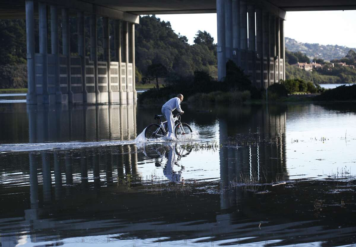 A cyclist pedals through a flood bike path near the the Manzanita Park And Ride after a record high tide known as a