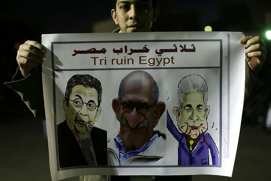 A supporter of President Mohammed Morsi holds a banner with caricatures of Morsi opponents during a protest in Giza. Photo: Hassan Ammar, Associated Press