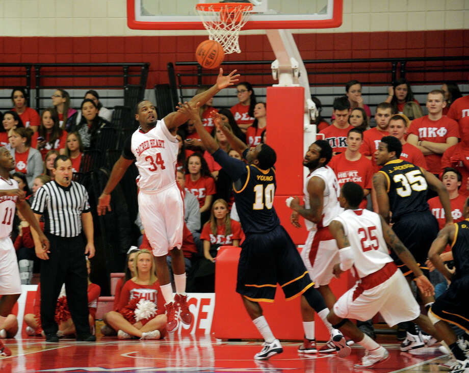 Highlights from men's basketball action between Sacred Heart and Quinnipiac at Sacred Heart University in Bridgeport, Conn. on Thursday January 19, 2012. Sacred Heart's #34 Stan Dulaire, left, blocks a Quinnipiac shot. Photo: Christian Abraham / Connecticut Post