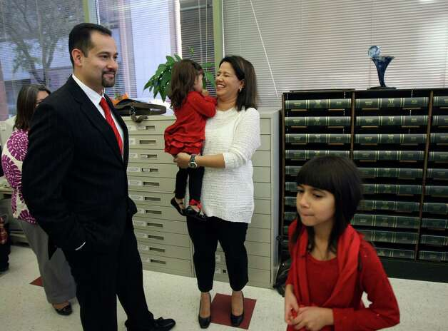 Rogelio Buentello and Cristina Garcia Buentello along with their two daughters Sofia, 2, and Emily, 8, wait to be married by County Clerk Gerry Rickhoff who performed more than 40 marriage ceremonies on Dec. 12, 2012. Photo: Helen L. Montoya, San Antonio Express-News / ©SAN ANTONIO EXPRESS-NEWS