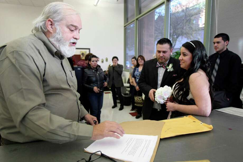"""In this file photo from December 2012, County Clerk Gerry Rickhoff performs the marriage ceremony of Andrew and Ana Villalobos. Rickhoff's defeat of longtime County Clerk Bob Green in 1994 signaled the end of the """"good ol' boy"""" system at the courthouse, for many. Photo: Helen L. Montoya, San Antonio Express-News / ©SAN ANTONIO EXPRESS-NEWS"""