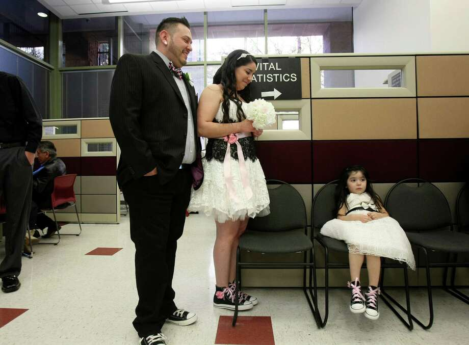 Anna and Andrew Villalobos wait with Ana's daughter Jayden Contreras, 3,  to are married by County Clerk Gerry Rickhoff who performed more than 40 marriage ceremonies on Dec. 12, 2012. Photo: Helen L. Montoya, San Antonio Express-News / ©SAN ANTONIO EXPRESS-NEWS