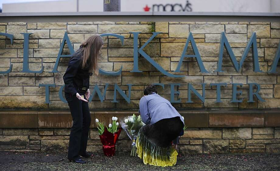 Tenille Beseda (left) and Leslie King place flowers at a Clackamas Town Center entrance. Photo: Greg Wahl-Stephens, Associated Press