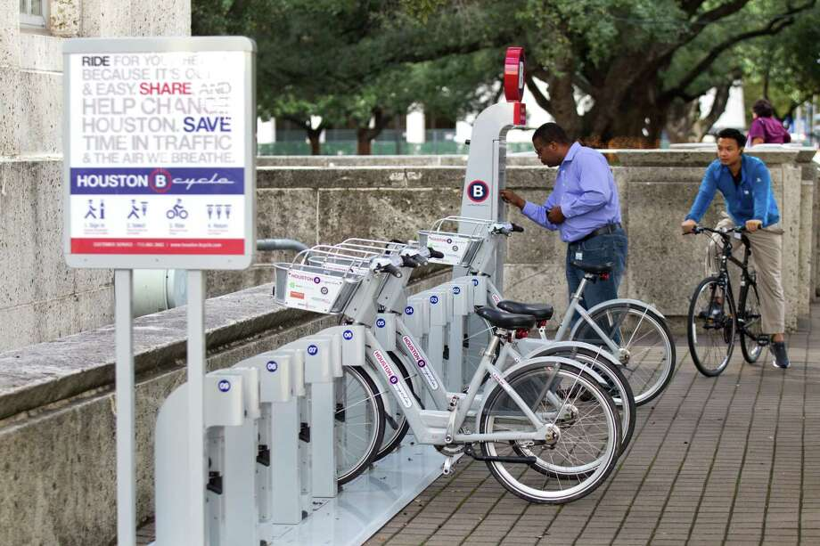 Richard Thomas checks out a B-Cycle rental bicycle last week near City Hall. Fees range from $5 for a pass that lasts 90 minutes to a $50 annual membership. Photo: Brett Coomer, Houston Chronicle / © 2012 Houston Chronicle
