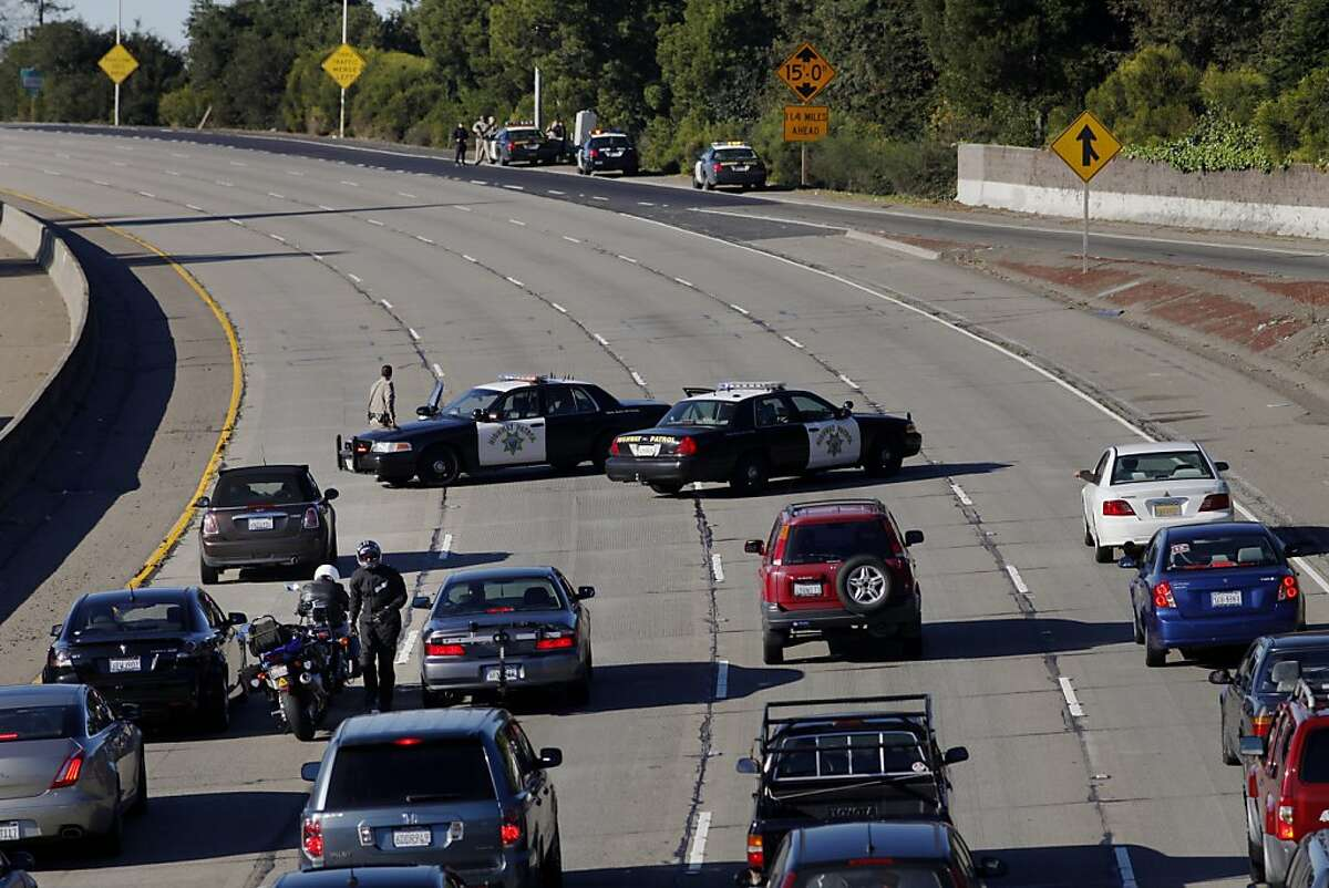 The California Highway Patrol blocks traffic as the Oakland Police Department searches for a suspect in a home invasion and armed robbery, Monday, Dec. 10, 2012.