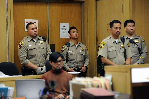 Court officers stand stand near the back of the court room during the proceedings.  An arraignment of five suspects held in connection with the slaying of a man found gagged and bound in Visitation Valley was held at the was held at the Hall of Justice at 850 Bryant St. in San Francisco, Ca Wednesday December 12th, 2012. Photo: Michael Short, Special To The Chronicle