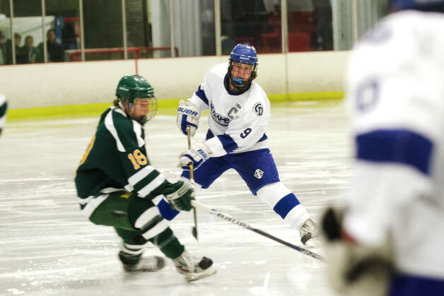 Darien's Dana Wensberg (9) passes the puck around Hamden's Matt Barnett (18) during the boys ice hockey game against Hamden High School at the Darien Ice Rink on Wednesday, Dec. 12, 2012. Photo: Amy Mortensen / Connecticut Post Freelance