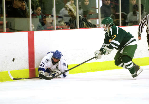 Darien's Brendan Hathaway (21) falls to the ice defending the puck against Hamden's Dan Chicoine (17) during the boys ice hockey game against Hamden High School at the Darien Ice Rink on Wednesday, Dec. 12, 2012. Photo: Amy Mortensen / Connecticut Post Freelance
