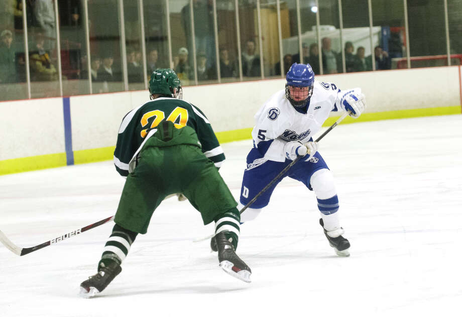 Darien's Owen Koorbusch (5) sizes up Hamden's Tim Gontarski (24) during the boys ice hockey game against Hamden High School at the Darien Ice Rink on Wednesday, Dec. 12, 2012. Photo: Amy Mortensen / Connecticut Post Freelance