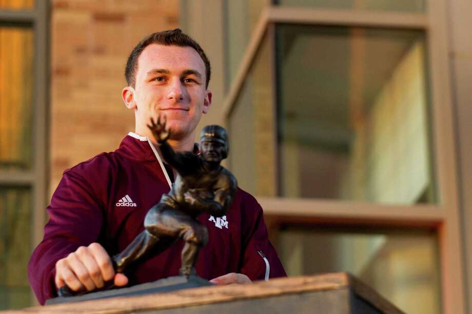 Texas A&M quarterback Johnny Manziel poses stands with his Heisman Trophy during a ceremony honoring him and three other Aggie football players Wednesday, Dec. 12, 2012, in College Station. Photo: Brett Coomer, Houston Chronicle / © 2012 Houston Chronicle