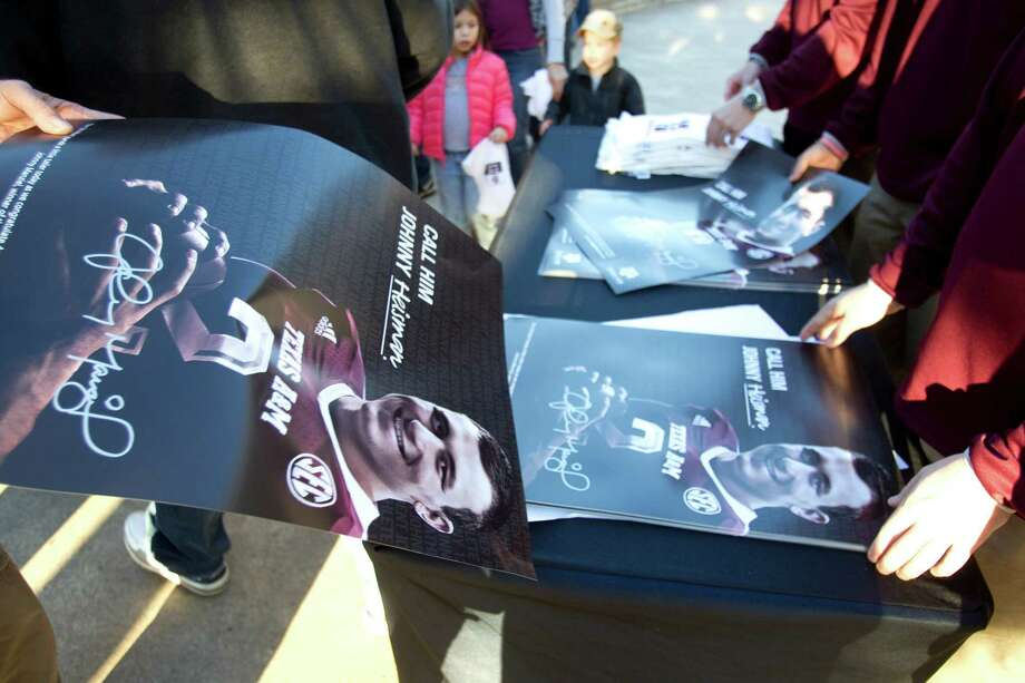 Posters with a picture of Heisman Trophy winner Johnny Manziel are handed out during a ceremony honoring Manziel and three other Aggie football players Wednesday, Dec. 12, 2012, in College Station. Photo: Brett Coomer, Houston Chronicle / © 2012 Houston Chronicle