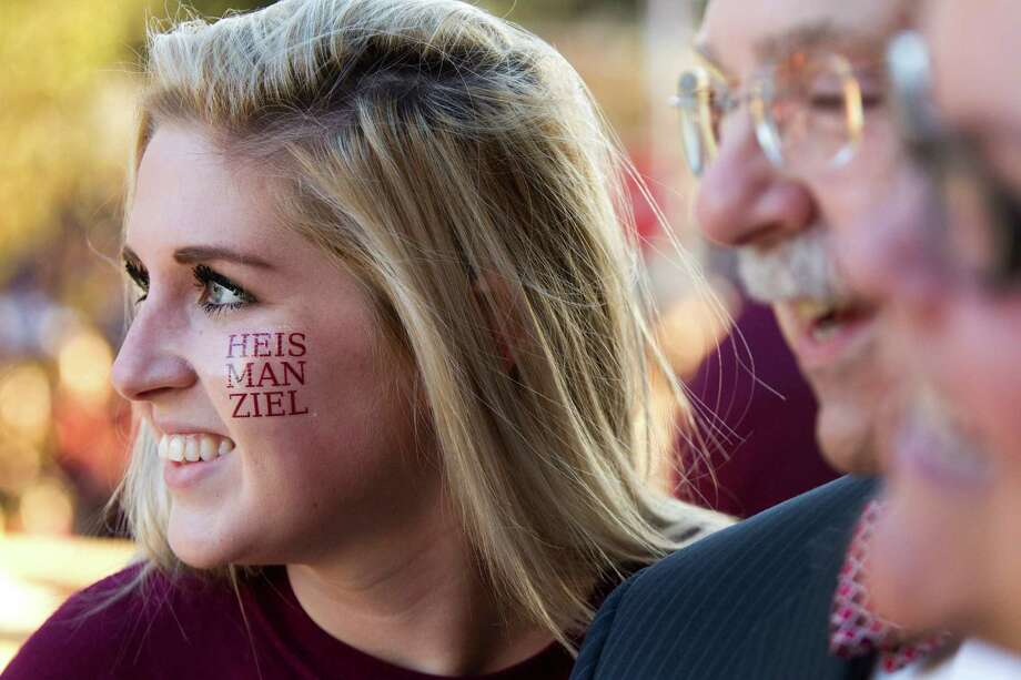 """Lauren Juliano wears a """"HEISMANZIEL"""" temporary tattoo on her face as she poses for a photo with Texas A&M President R. Bowen Loftin during a ceremony honoring Heisman Trophy winner Johnny Manziel and three other Aggie football players Wednesday, Dec. 12, 2012, in College Station. Photo: Brett Coomer, Houston Chronicle / © 2012 Houston Chronicle"""