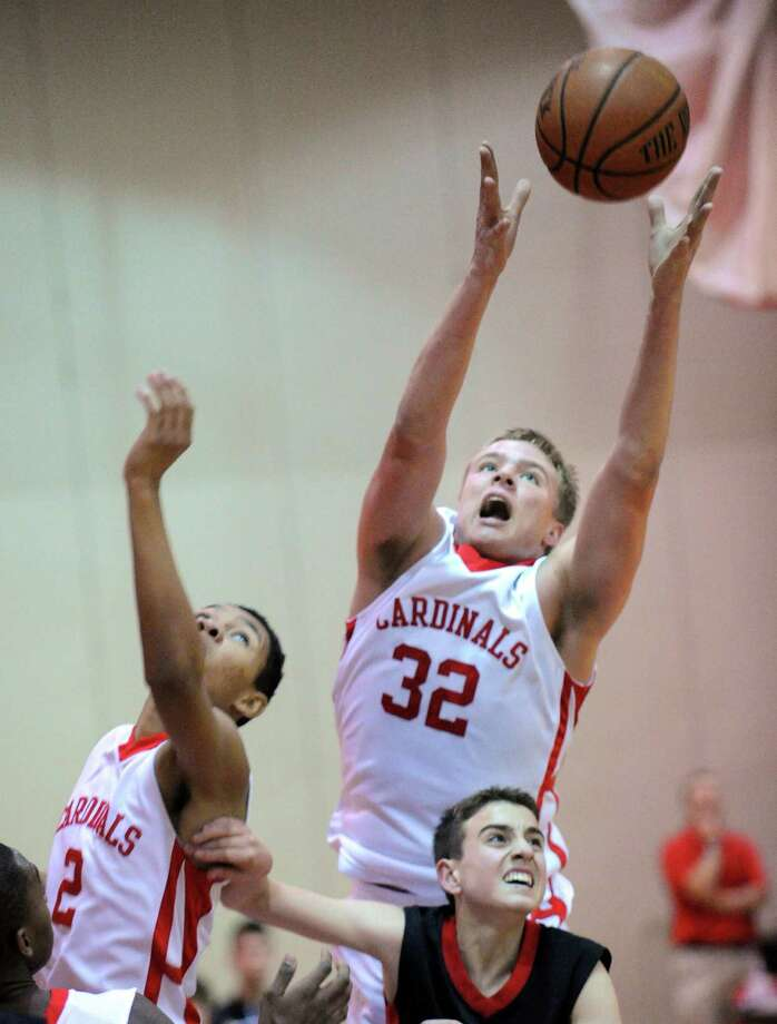 At right, Alex Wolf (# 32) of Greenwich grabs a rebound over Fairfield Warde's Hunter Smaldone as CJ Byrd, left, of Greenwich, goes for the ball during the boys high school basketball game between Greenwich HIgh School and Fairfield Warde High School at Greenwich High School, Wednesday night, Dec. 12, 2012. Photo: Bob Luckey / Greenwich Time