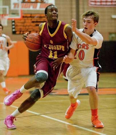 St. Joseph High School's Quincy McKnight keeps the ball away from Ridgefield High School's Matthew Brennan in a game at Ridgefield. Wednesday, Dec. 12, 2012 Photo: Scott Mullin / The News-Times Freelance