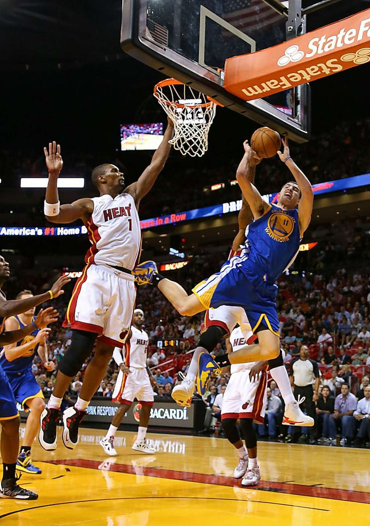 MIAMI, FL - DECEMBER 12: Klay Thompson #11 of the Golden State Warriors shoots over Chris Bosh #1 of the Miami Heat during a game at American Airlines Arena on December 12, 2012 in Miami, Florida. (Photo by Mike Ehrmann/Getty Images)