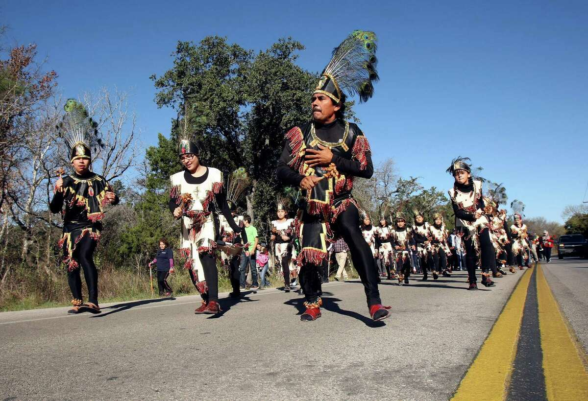 Banda Azteca Guadalupana members lead the way along Riggs Road in Helotes as parishioners walk from Our Lady of Guadalupe Church in Helotes to the parish of the same name on San Antonio's West Side.
