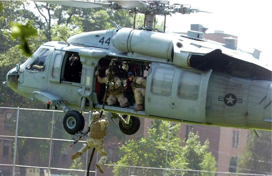 In this file photo, Navy SEALs drop out of a Sikorsky-made MH-60 Black Hawk helicopter during a demonstration of combat techniques at an annual salute to veterans in Greenwich, Conn. Photo: John Nickerson, ST / Stamford Advocate