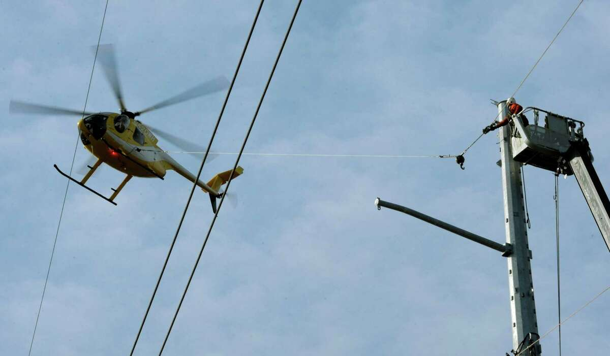 A lineman from PAR Electrical Contractors, along with a sub-contracted helicopter, string lead lines that will be used to pull new electrical transmission cables along a 6,700-foot area of Waterford, Conn., crossing Rt. 1 near Cross Road Monday, December 3, 2012. The helicopter speeds up the process of stringing the new transmission lines across difficult terrain. The new transmission lines will bolster the durability of the feed from Millstone Nuclear Power Station through eastern Connecticut and into the New England power grid. (AP Photo/The Day, Sean D. Elliot)