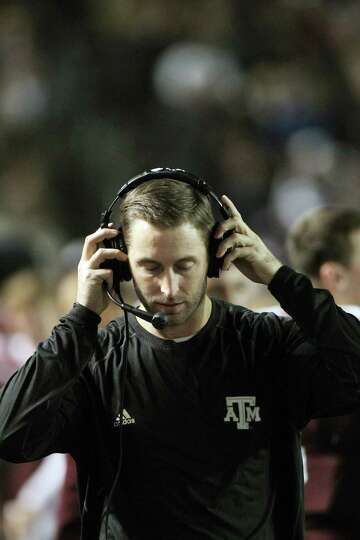 Texas A&M offensive coordinator Kliff Kingsbury adjusts his headset as he paces the sidelines ag