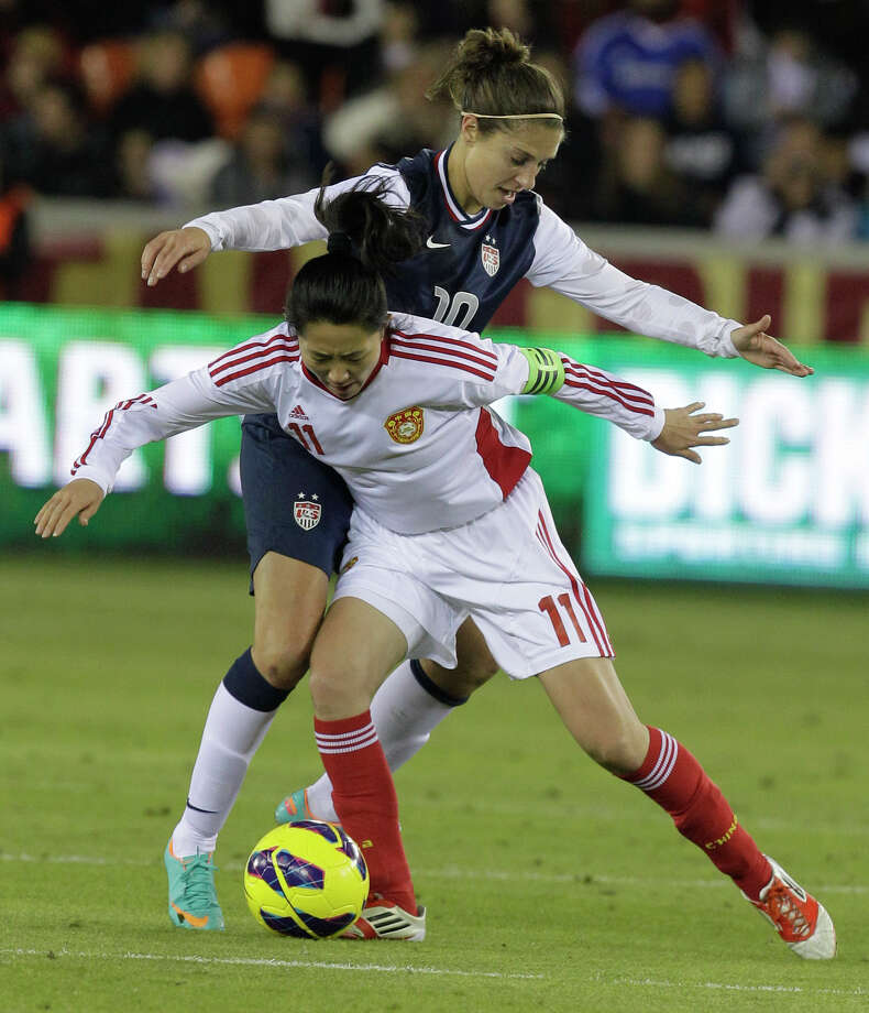 USA's Carli Lloyd and China's Pu Wei tangle for the ball during woman's soccer game at BBVA Compass Stadium Sunday, Jan. 9, 2000, in Houston. Photo: Melissa Phillip, Houston Chronicle / © 2012 Houston Chronicle