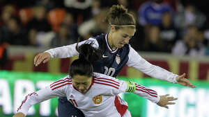USA's Carli Lloyd and China's Pu Wei tangle for the ball during woman's soccer game at BBVA Compass Stadium Sunday, Jan. 9, 2000, in Houston.