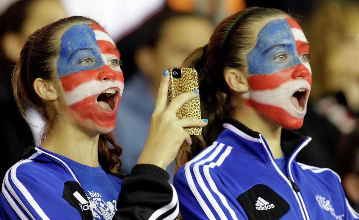 Eleven-years-old twins Emma Dyson, left, and Avery Dyson, right, cheer for the USA Women's soccer team before game against China at BBVA Compass Stadium Sunday, Jan. 9, 2000, in Houston.