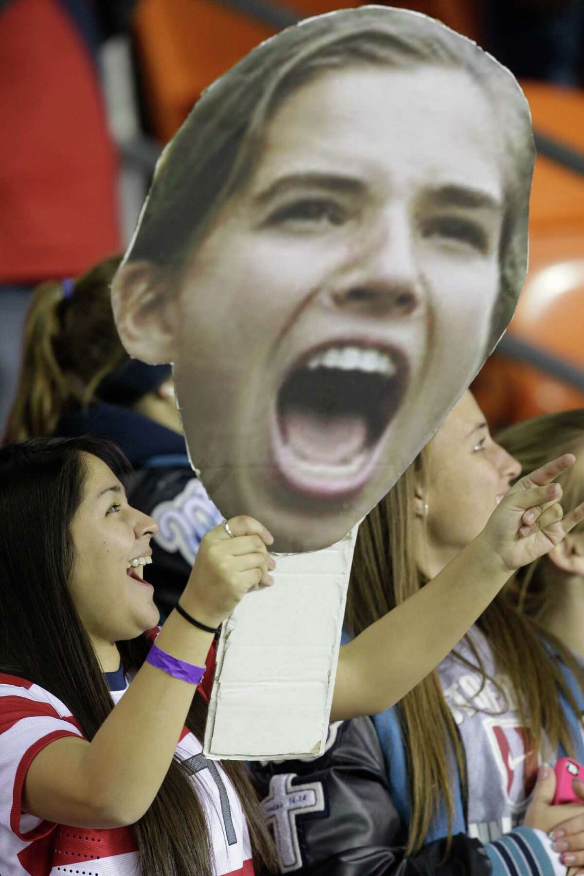 Alexis Beas of Ft. Smith, AR holds a sign with the face of USA's Tobin Heath as she cheers for the USA Women's soccer team before game against China at BBVA Compass Stadium Sunday, Jan. 9, 2000, in Houston.