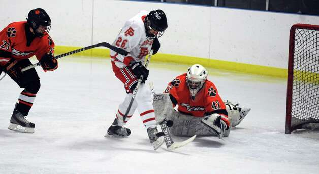 Fairfield Prep's Matt McKinney tries to get the puck past Ridgefield goalie Dusty Rausa during their hockey game Wednesday, Dec. 12, 2012 at Wonderland of Ice in Bridgeport, Conn. Photo: Autumn Driscoll / Connecticut Post