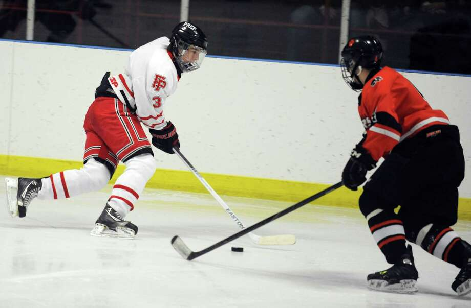 Fairfield Prep's Matt Wikman controls the puck as Ridgefield's Henry Gough defends during their hockey game Wednesday, Dec. 12, 2012 at Wonderland of Ice in Bridgeport, Conn. Photo: Autumn Driscoll / Connecticut Post