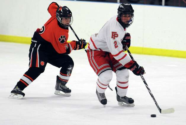 Fairfield Prep's Andrew Hatton controls the puck as Ridgefield's Vinny Rella defends during their hockey game Wednesday, Dec. 12, 2012 at Wonderland of Ice in Bridgeport, Conn. Photo: Autumn Driscoll / Connecticut Post