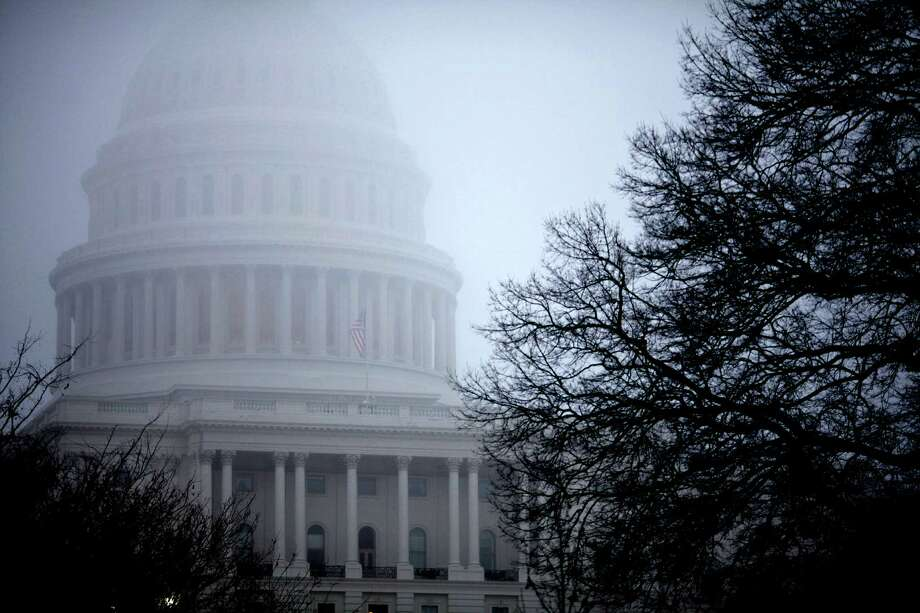 FILE - In this Monday, Dec. 10, 2012, file  photo, fog obscures the Capitol dome on Capitol Hill in Washington. Even if Congress and the White House fail to strike a budget deal by New Year's Day, reality may be a lot less bleak then the scenario that's been spooking employers and investors and slowing the U.S. Economy. The tax increases and spending cuts could be retroactively repealed after Jan. (AP Photo/J. Scott Applewhite, File) Photo: J. Scott Applewhite