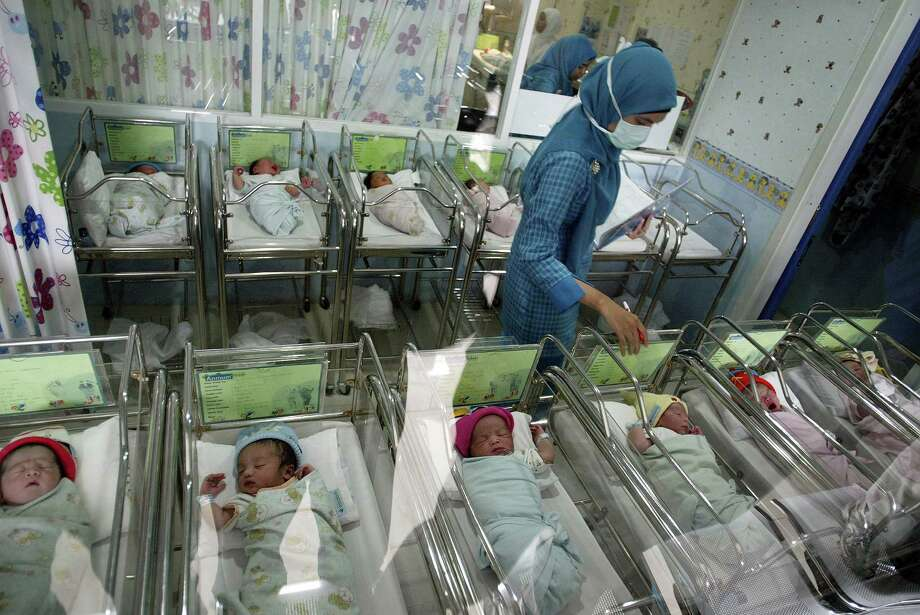 A nurse at the Mother and Child Hospital in Surabaya in East Java province looks after 13 newborn babies born on December 12, 2012. Several hospitals in Indonesia's main cities performed more Caesarians than usual with new mothers hoping a 12-12-12 birth date will bring luck to their newborns. Photo: JUNI KRISWANTO, AFP/Getty Images / AFP