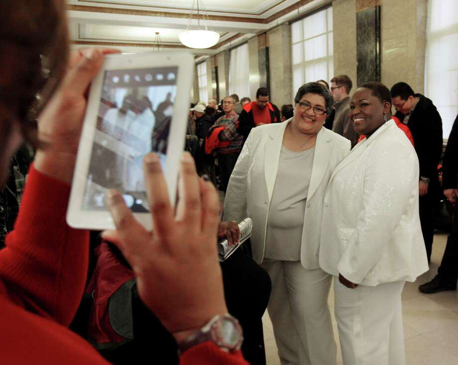 Carmen Bell-Delgado, center, and Tonia Bell-Delgado, of Winter Haven, Fla., right, pose for a photo before their wedding in the Office of the City Clerk, in New York, Wednesday, Dec. 12, 2012. The Bell-Delgados were married in New York because same-sex marriages are not legal in their home state. New York Mayor Michael Bloomberg turned the Manhattan Marriage Bureau into a gleaming 24,000-square-foot wedding palace in 2009, saying he was setting out to give Vegas a run for its money. Photo: Richard Drew, Associated Press / AP